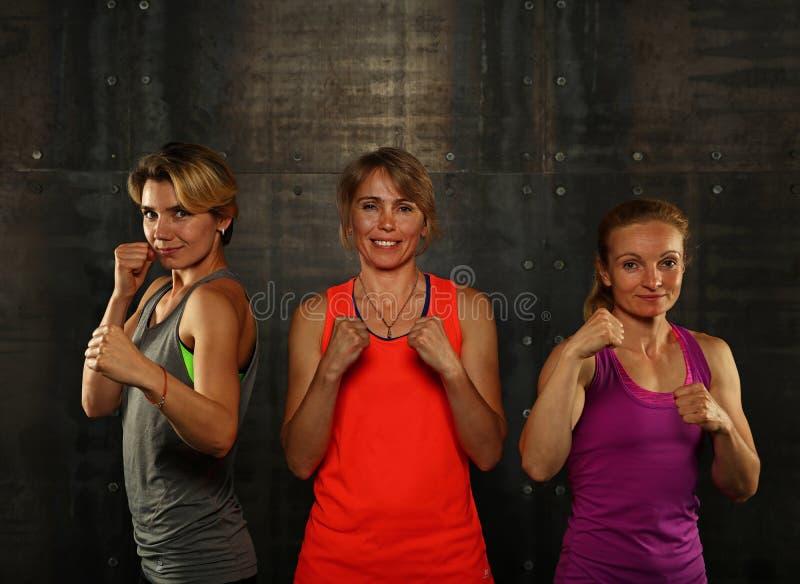 Retrato de tres mujeres atléticas jovenes en gimnasio fotos de archivo libres de regalías