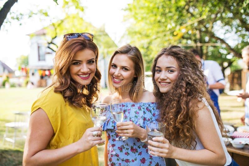 Retrato de tres mujeres en una celebración de familia o un partido de la barbacoa afuera en el patio trasero imágenes de archivo libres de regalías