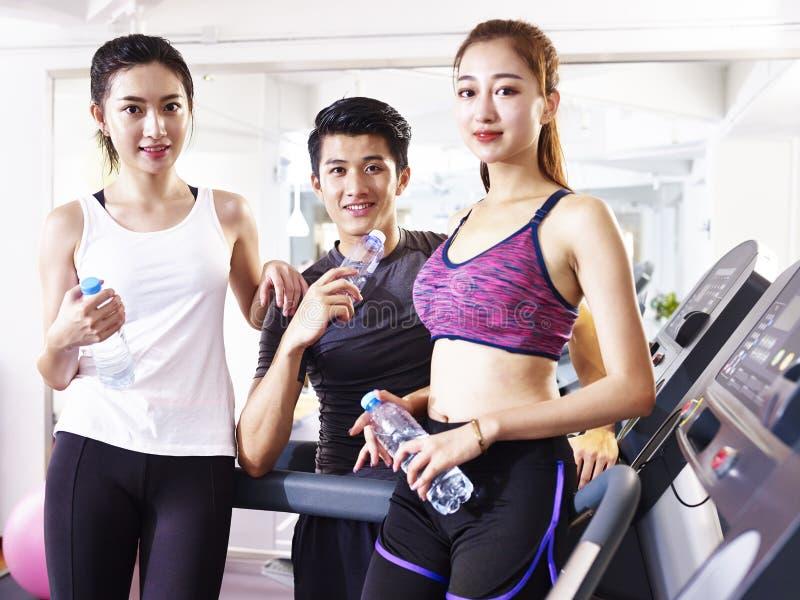 Retrato de tres personas asiáticas jovenes en gimnasio imagen de archivo libre de regalías