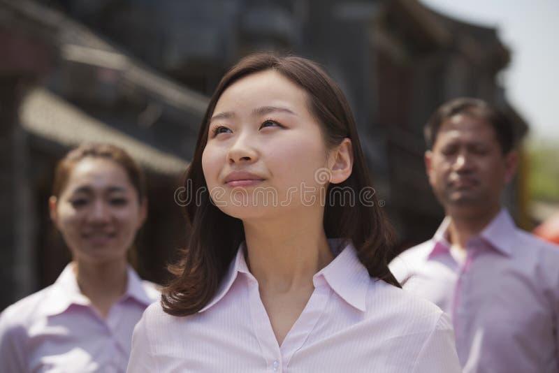 Retrato de tres personas confiadas bien vestidas en Pekín, China foto de archivo