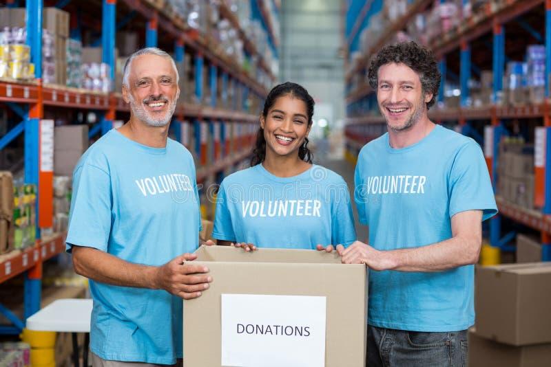 Retrato de tres voluntarios que sostienen una caja de las donaciones foto de archivo libre de regalías