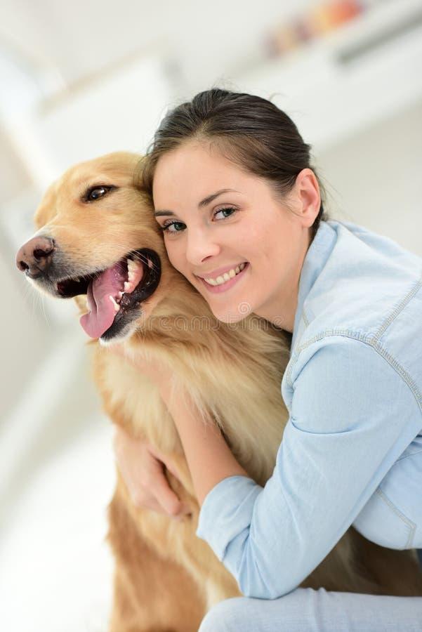 Retrato de trocas de carícias da jovem mulher seu cão foto de stock