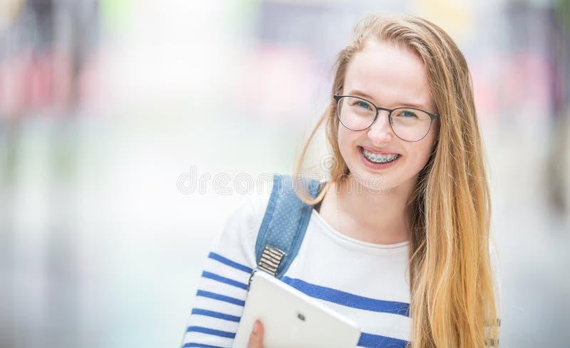 Retrato de um adolescente bonito de sorriso com cintas dentais Estudante nova com saco de escola e dispositivo da tabuleta imagens de stock