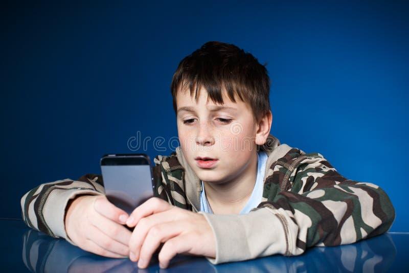 Retrato de um adolescente com um telefone imagens de stock