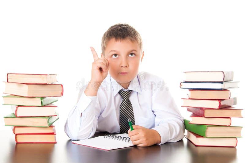 Retrato de um adolescente do menino na escola na biblioteca perto da pilha de livros Inventada, veio a inspiração Estudante engra fotografia de stock royalty free
