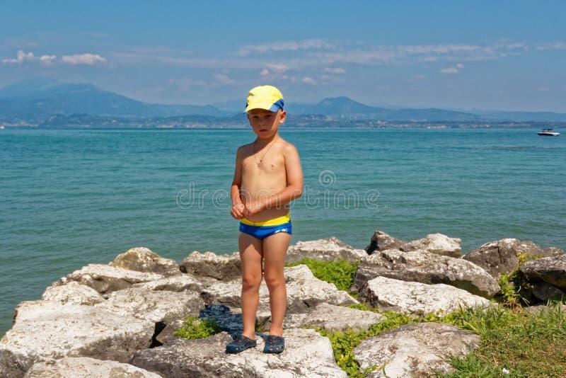Retrato de um adolescente em troncos de natação na praia imagem de stock