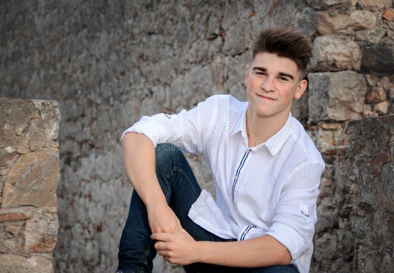 Retrato de um adolescente Está sentando-se em uma parede de pedra imagem de stock royalty free