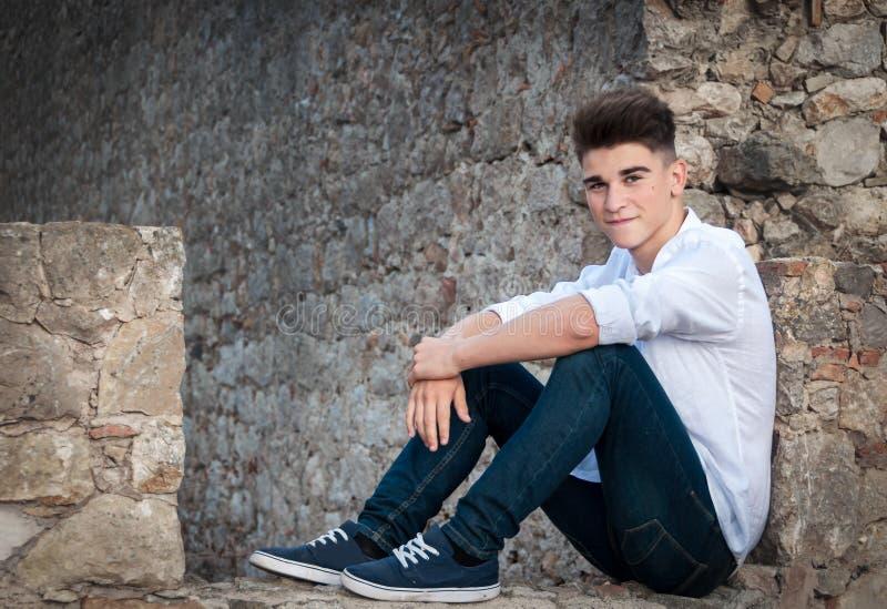Retrato de um adolescente Está sentando-se em uma parede de pedra dramático imagens de stock