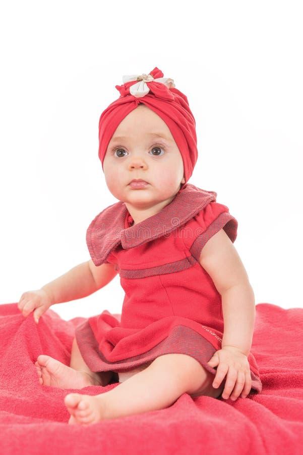 Retrato de um agradável do bebê vestido na roupa vermelha que procura a atenção imagens de stock