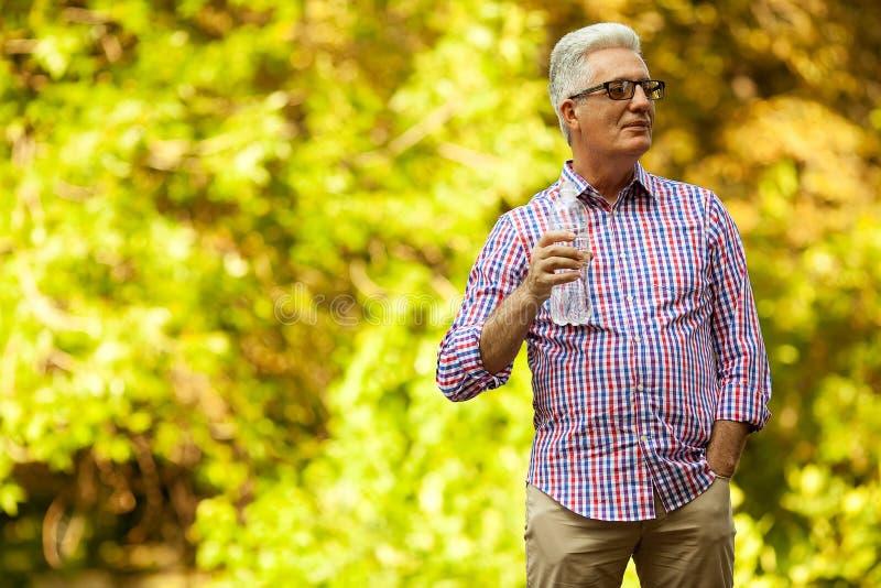 Retrato de um ancião maduro em beber ocasional na moda da camisa foto de stock royalty free