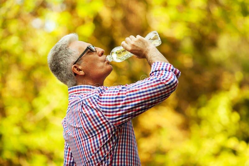 Retrato de um ancião maduro na camisa ocasional na moda e no glasse imagens de stock royalty free