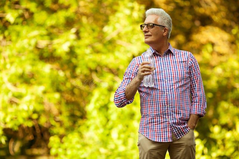 Retrato de um ancião maduro na camisa ocasional na moda e no glasse fotografia de stock