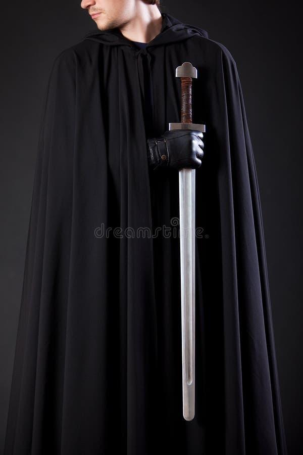 Retrato de um andarilho corajoso do guerreiro em um casaco e em uma espada pretos à disposição foto de stock royalty free