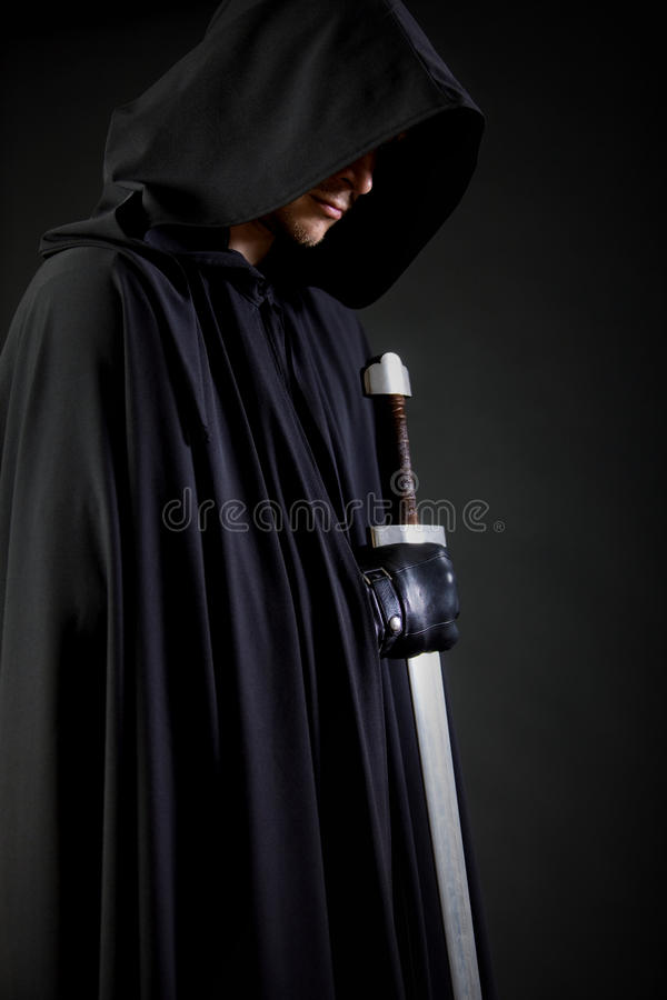 Retrato de um andarilho corajoso do guerreiro em um casaco e em uma espada pretos à disposição fotos de stock