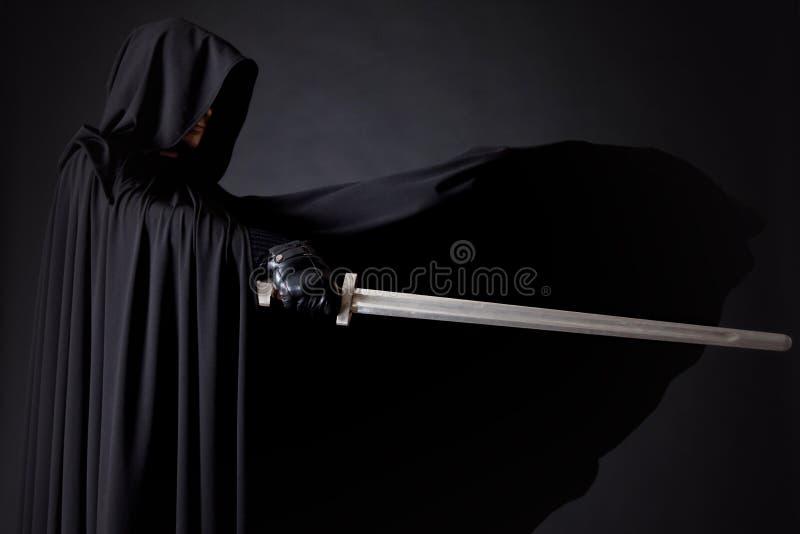 Retrato de um andarilho corajoso do guerreiro em um casaco e em uma espada pretos à disposição fotografia de stock royalty free