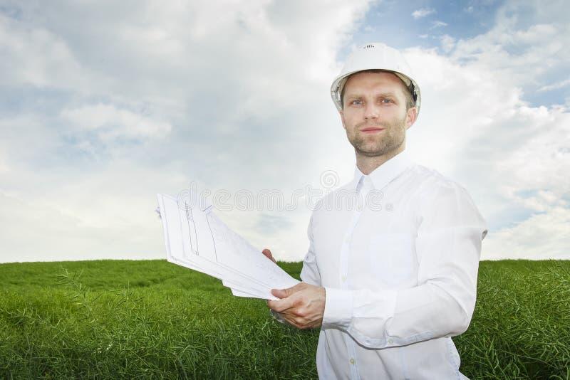 Retrato de um arquiteto com desenhos em um capacete branco em um canteiro de obras novas fotos de stock