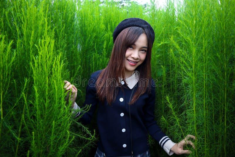 Retrato de um asiático bonito novo da mulher no jardim, é bonito e sorrindo felizmente foto de stock royalty free