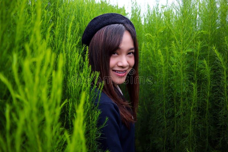 Retrato de um asiático bonito novo da mulher no jardim, é bonito e sorrindo felizmente foto de stock