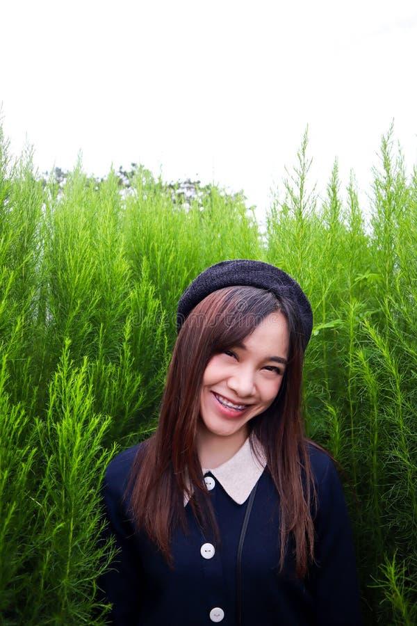 Retrato de um asiático bonito novo da mulher no jardim, é bonito e sorrindo felizmente fotografia de stock royalty free