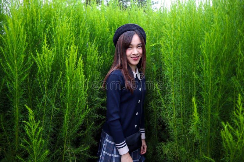 Retrato de um asiático bonito novo da mulher no jardim, é bonito e sorrindo felizmente fotos de stock