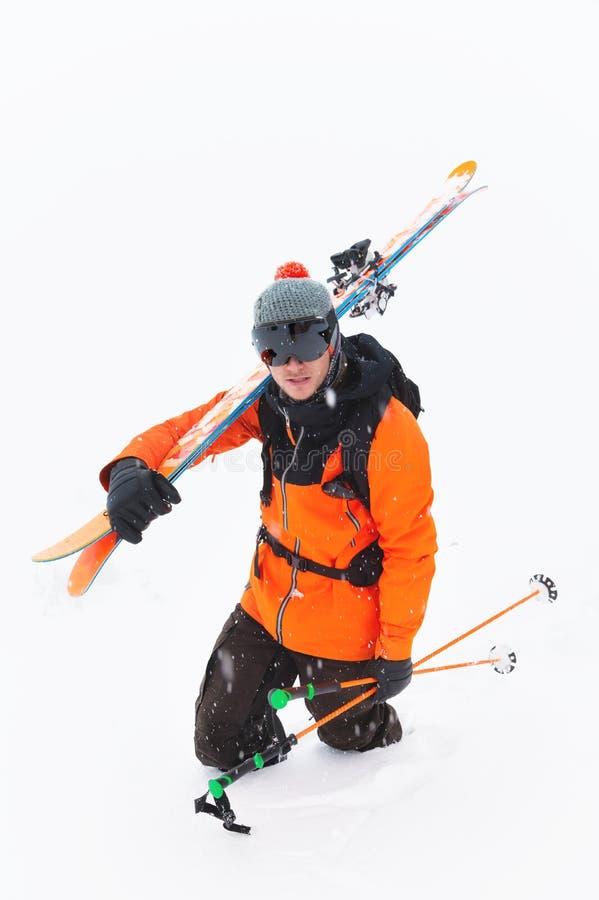 Retrato de um atleta profissional do esquiador em um chapéu feito malha e do terno alaranjado-preto com uma máscara de esqui pret imagem de stock