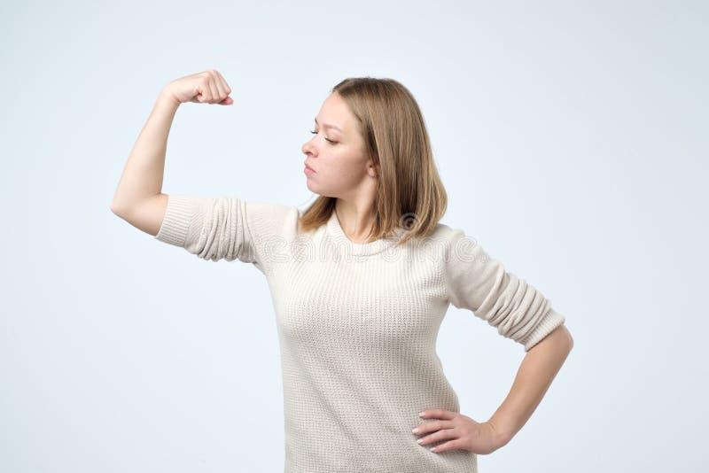 Retrato de um bíceps forte da exibição da moça que é auto-confiante e forte imagens de stock