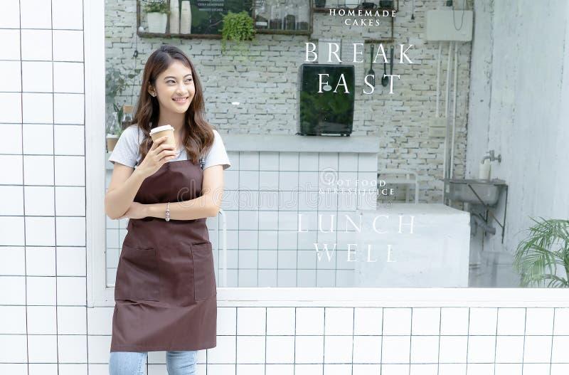 Retrato de um barista asiático novo feliz no avental que guarda o café quente e que está na frente de sua cafetaria pequena Parti fotografia de stock royalty free