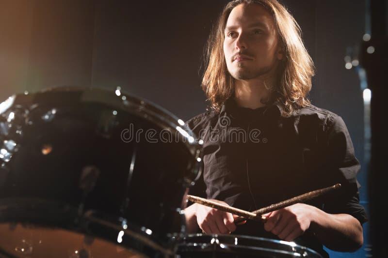 Retrato de um baterista de cabelos compridos com os hashis em suas mãos que sentam-se atrás de um grupo do cilindro Baixa chave C imagens de stock