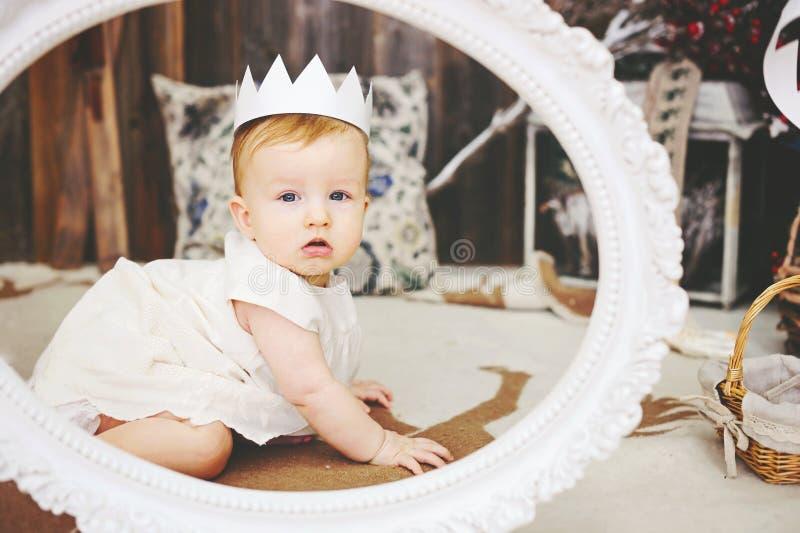 Retrato de um bebê bonito com coroa de papel imagem de stock