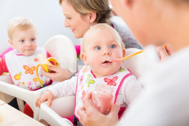 Retrato de um bebê bonito e saudável com os olhos azuis que olham sua mãe imagens de stock