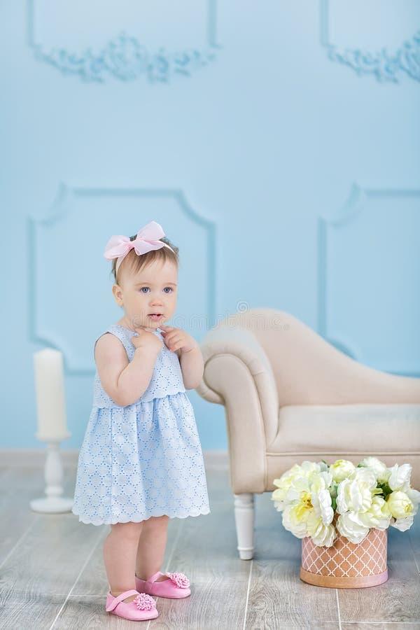 Retrato de um bebê bonito em um fundo claro com uma grinalda das flores em sua cabeça que senta-se na cesta do sofá imagem de stock royalty free