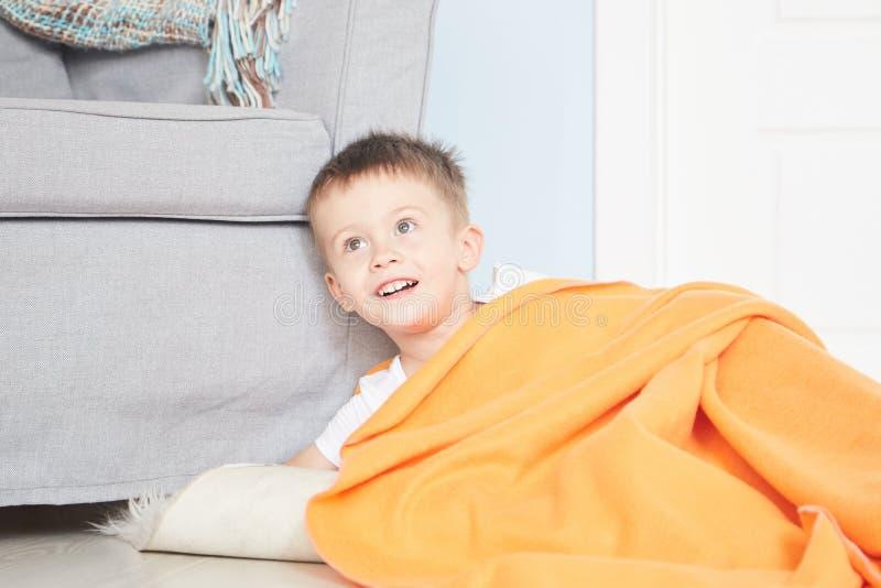 Retrato de um bebê bonito na manta alaranjada na casa foto de stock