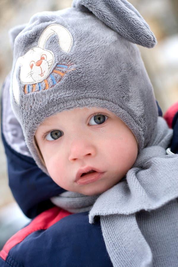 Retrato de um bebê bonito que desgasta um chapéu do inverno imagem de stock