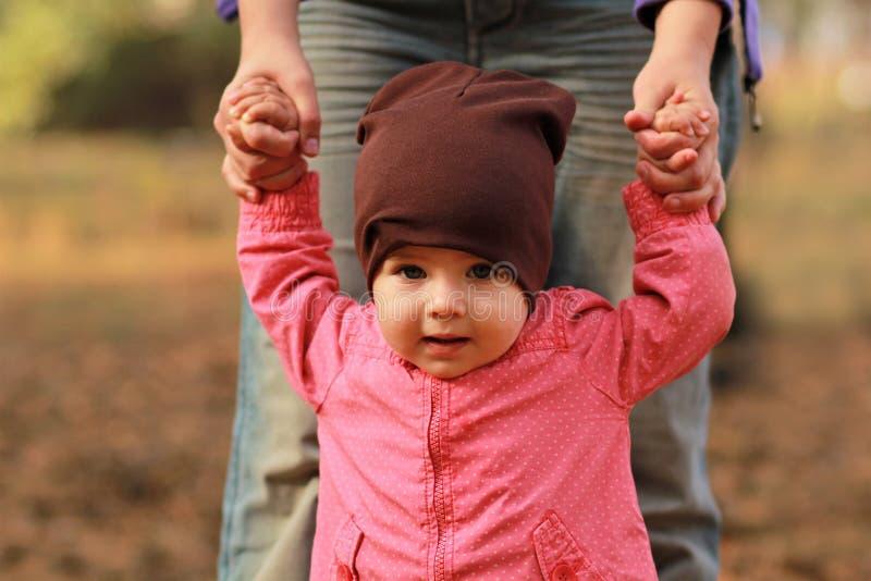 Retrato de um bebê bonito que guarda as mãos do ` s da mamã e que aprende andar fotos de stock royalty free