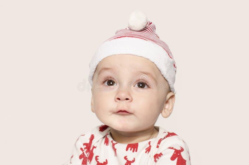 Retrato de um bebê bonito que olha acima de pensamento vestindo um chapéu de Santa fotografia de stock