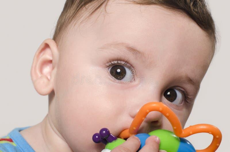 Retrato de um bebê bonito que senta-se e que joga com brinquedos foto de stock