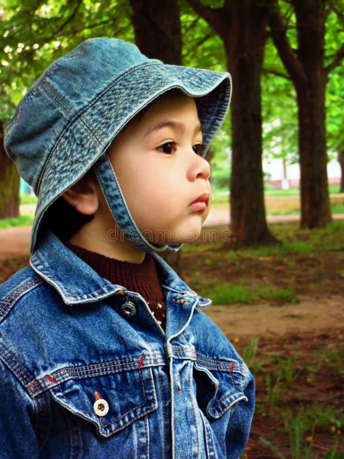 Retrato de um bebê em um revestimento da sarja de Nimes e em um chapéu de Panamá imagem de stock
