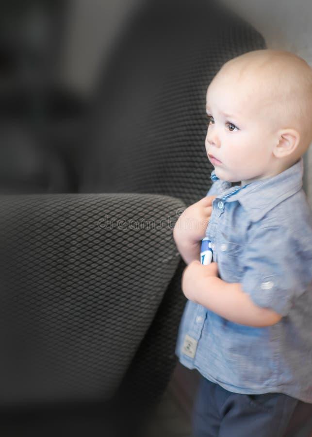 Retrato de um bebê idoso pequeno de 1,5 anos que está no roon escuro sob a parede e que olha assustado Medo ou punição da foto de stock royalty free