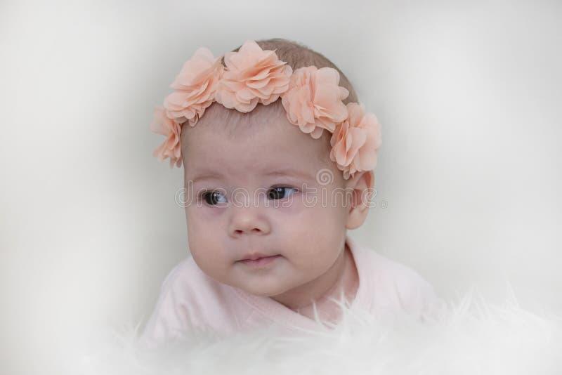 Retrato de um bebê 3 meses que aprendem guardar a cabeça, flores cor-de-rosa na cabeça Foco macio do close-up do retrato da crian imagens de stock