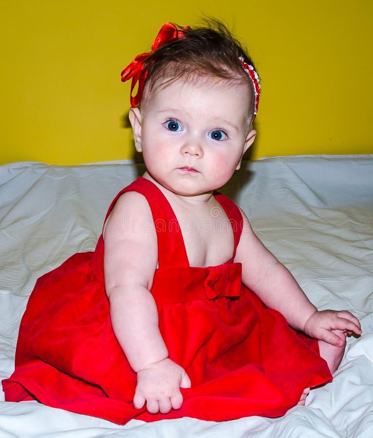 Retrato de um bebê pequeno bonito em um vestido vermelho com uma curva em sua cabeça foto de stock royalty free