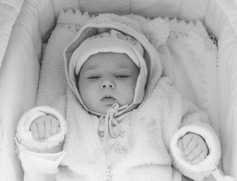 Retrato de um bebê de três meses sonolento que encontra-se em um berço na roupa cor-de-rosa, vista superior preto e branco foto de stock royalty free