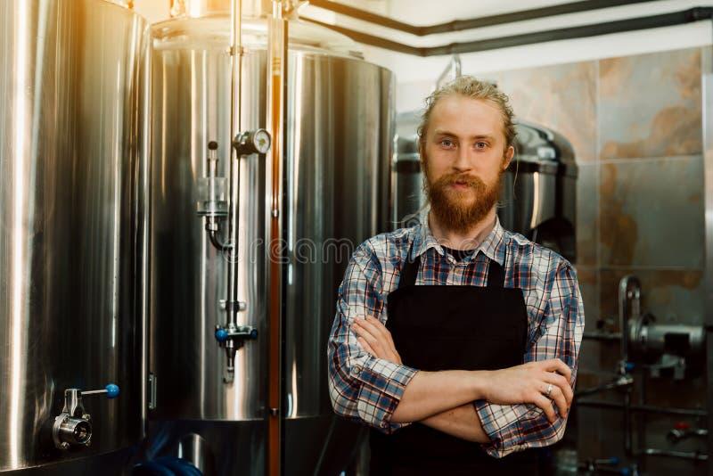 Retrato de um bonito produtor de cerveja, com travas em uniforme, no fabrico de cerveja, com recipientes metálicos sobre fundo fotos de stock