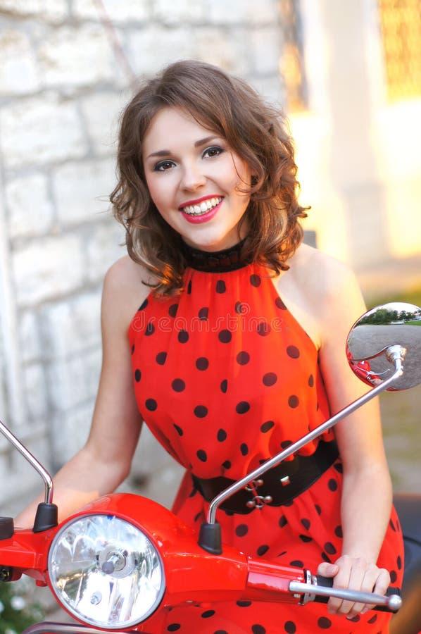 Retrato de um brunette novo em um 'trotinette' vermelho velho imagem de stock