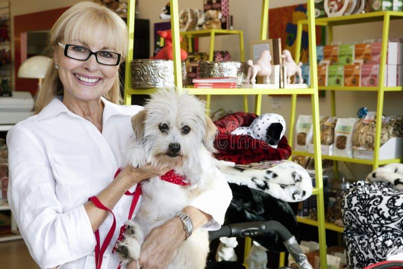 Retrato de um cão levando da mulher superior feliz na loja de animais de estimação imagens de stock