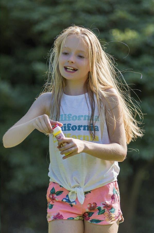 Retrato de um cabelo louro longo do adolescente, tendo o divertimento nas bolhas de sopro do jardim imagem de stock