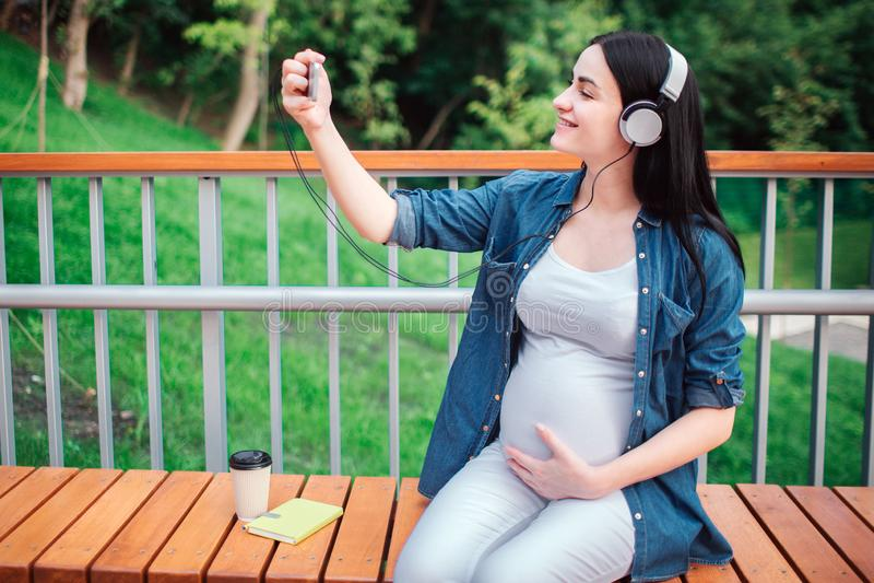 Retrato de um cabelo preto feliz e de uma mulher gravida orgulhosa em uma cidade no fundo Está sentando-se em um banco da cidade imagens de stock