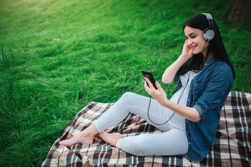 Retrato de um cabelo preto feliz e de uma mulher gravida orgulhosa em uma cidade no fundo Está sentando-se em um banco da cidade imagem de stock
