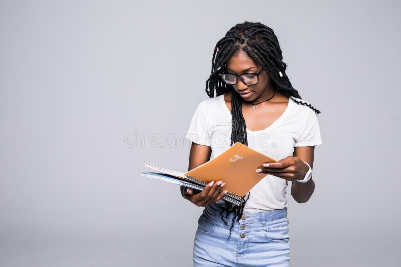 Retrato de um caderno afro-americano de sorriso da terra arrendada da mulher sobre o fundo cinzento imagem de stock