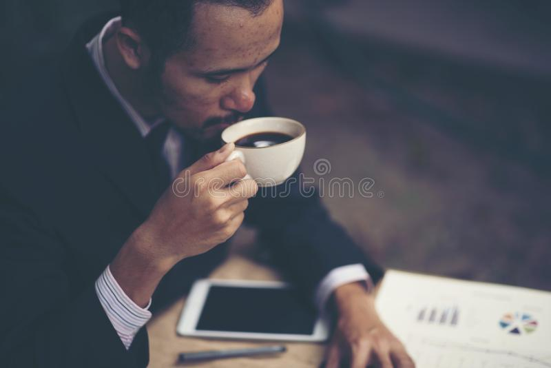Retrato de um café bebendo do homem de negócios novo ao sentar a OU imagem de stock royalty free