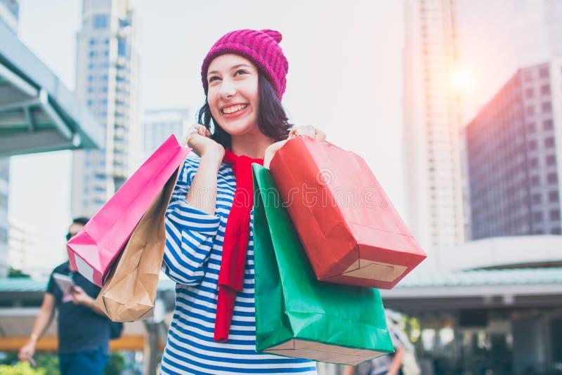 Retrato de um chapéu bonito entusiasmado da camisa e das lãs do desgaste da moça que guarda muitos sacos de compras e sorriso Com fotografia de stock royalty free